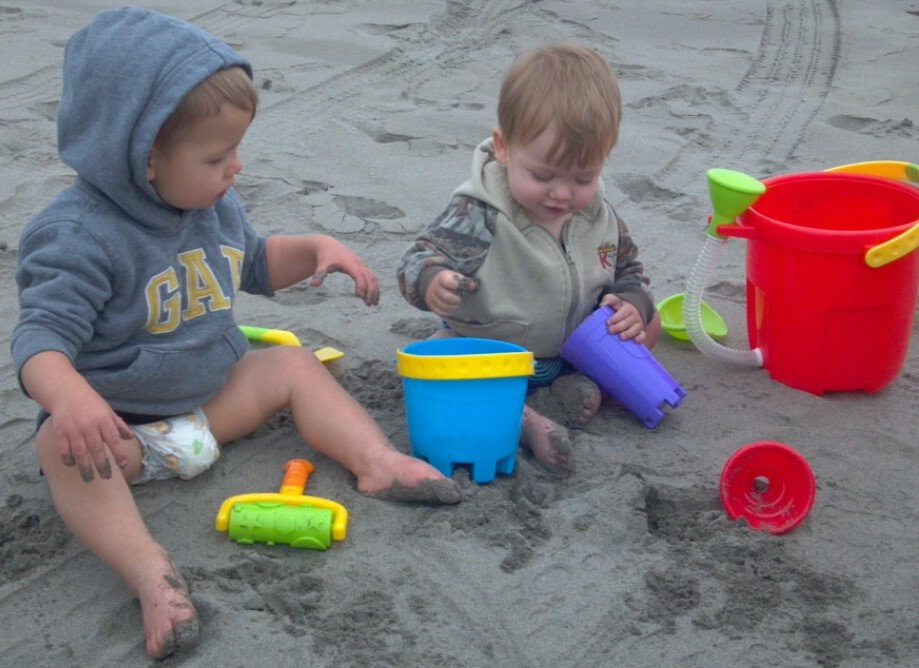 Baby boys playing with their toys in the Long Beach sand