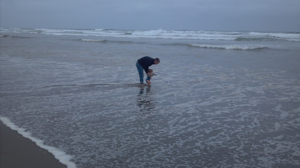 Father and son playing in the ocean surf