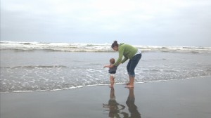 Playing with baby on the shore of the beach.